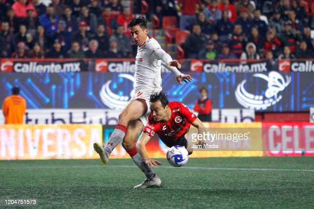Adrian Mora of Toluca struggles for the ball against Erick Torres of Tijuana during the 5th round match between Tijuana and Toluca as part of the...
