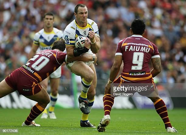 Adrian Morley of Warrington is brought down by Scott Moore L and David Faiumu of Huddersfield during the Carnegie Challenge Cup Final between...