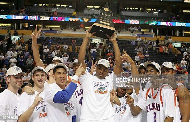 Adrian Moss of the Florida Gators celebrates with the SEC championship conference trophy along with his teammates following Florida's 49-47 win over...