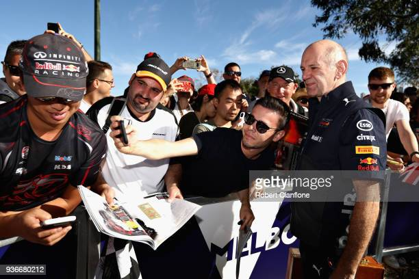 Adrian Newey the Chief Technical Officer of Red Bull Racing arrives at the circuit and poses for a photo with a fan before practice for the...