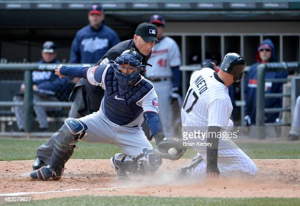 Adrian Nieto of the Chicago White Sox scores past catcher Kurt Suzuki of the Minnesota Twins on an RBI single hit by Leury Garcia during the ninth...