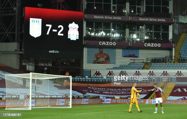 Adrian of Liverpool shakes hands with Ollie Watkins of Aston Villa as the final score of 7-2 is seen on the big screen behind during the Premier...