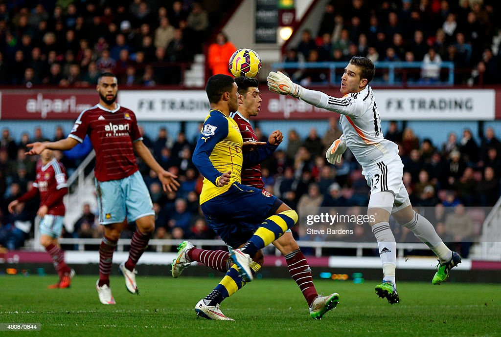 Adrian of West Ham punches clear from Alex Oxlade-Chamberlain of Arsenal during the Barclays Premier League match between West Ham United and Arsenal at Boleyn Ground on December 28, 2014 in London, England.