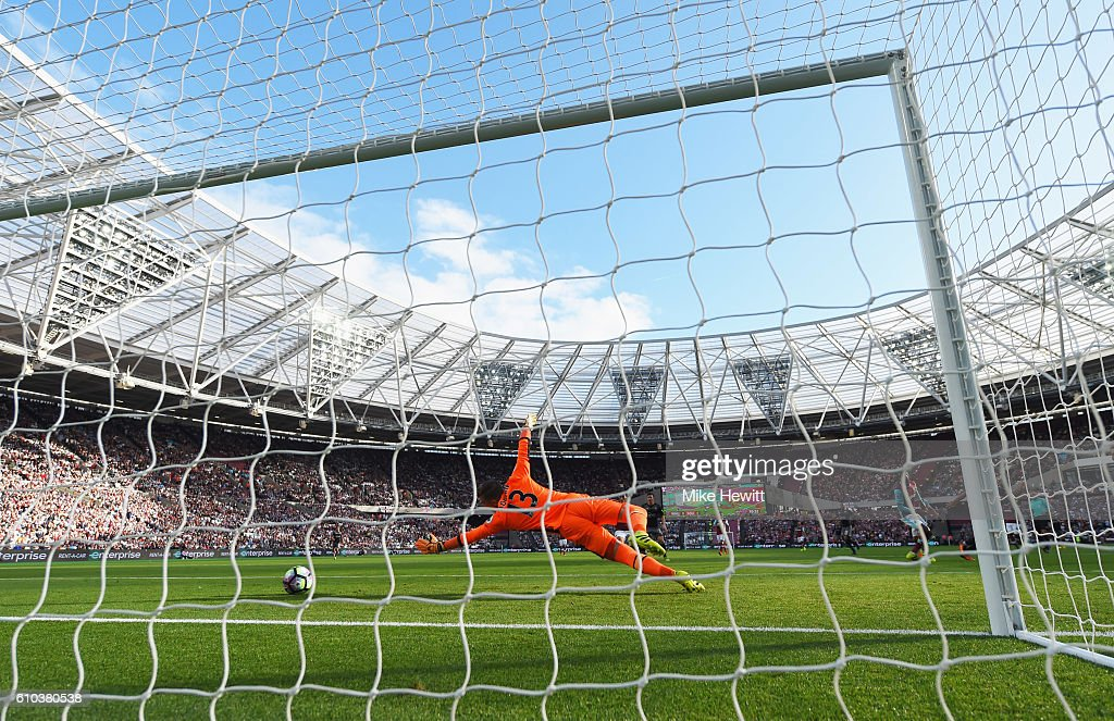 Adrian of West Ham United dives in vain as Charlie Austin of Southampton (obscured) scores their first goal during the Premier League match between West Ham United and Southampton at London Stadium on September 25, 2016 in London, England.