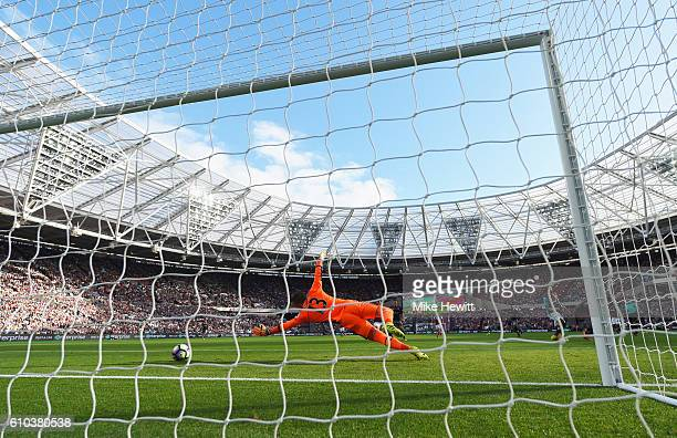 Adrian of West Ham United dives in vain as Charlie Austin of Southampton scores their first goal during the Premier League match between West Ham...