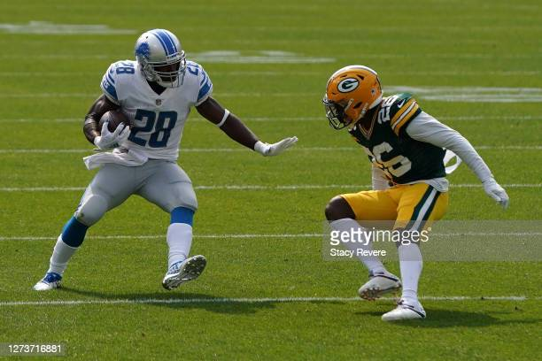 Adrian Peterson of the Detroit Lions avoids a tackle by Darnell Savage of the Green Bay Packers during the first quarter at Lambeau Field on...
