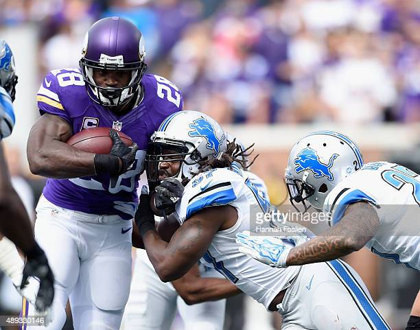 Adrian Peterson of the Minnesota Vikings carries the ball against Josh Bynes of the Detroit Lions during the first quarter of the game on September...