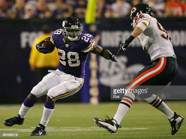 Adrian Peterson of the Minnesota Vikings carries the ball as Hunter Hillenmeyer of the Chicago Bears defends on November 29 2009 at Hubert H Humphrey...
