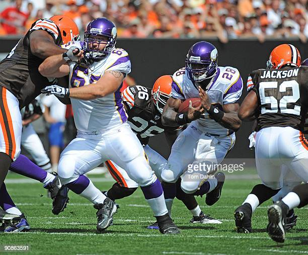 Adrian Peterson of the Minnesota Vikings carries the ball behind a block by teammate John Sullivan during an NFL game against the Cleveland Browns...