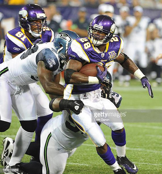 Adrian Peterson of the Minnesota Vikings carries the ball during an NFL preseason game against the Seattle Seahawks at the Mall of America Field at...