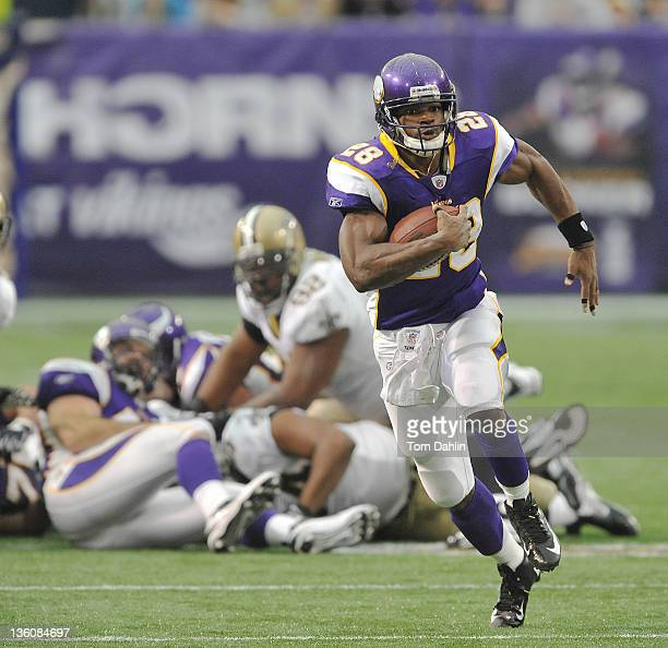 Adrian Peterson of the Minnesota Vikings carries the ball during an NFL game against the New Orleans Saints at the Hubert H Humphrey Metrodome on...