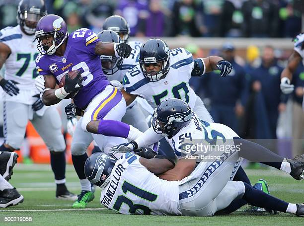 Adrian Peterson of the Minnesota Vikings gets tackled by Kam Chancellor of the Seattle Seahawks in the first quarter on December 6 2015 at TCF Bank...