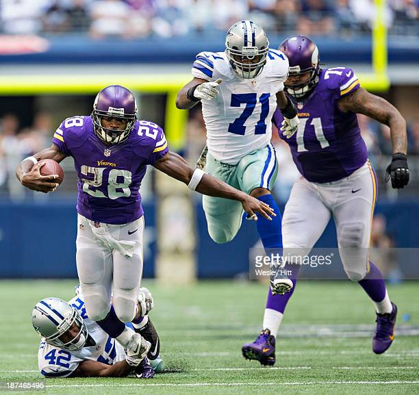 Adrian Peterson of the Minnesota Vikings is tackled by Barry Church of the Dallas Cowboys at ATT Stadium on November 3 2013 in Arlington Texas The...