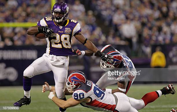 Adrian Peterson of the Minnesota Vikings is tackled by Chris Kelsay of the Buffalo Bills at the Mall of America Field at the Hubert H Humphrey...