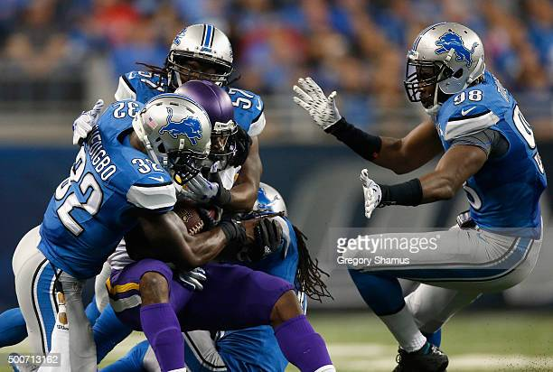 Adrian Peterson of the Minnesota Vikings is tackled by James Ihedigbo, Josh Bynes, and Rashean Mathis of the Detroit Lions at Ford Field on October...