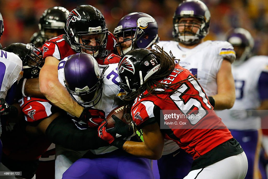 Adrian Peterson #28 of the Minnesota Vikings is tackled by Philip Wheeler #51 and Kroy Biermann #71 of the Atlanta Falcons during the second half at the Georgia Dome on November 29, 2015 in Atlanta, Georgia.