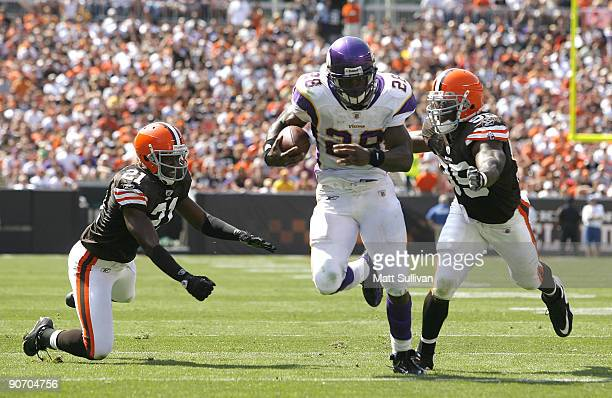 Adrian Peterson of the Minnesota Vikings runs by Brodney Pool and Corey Willams of the Cleveland Brwons at Cleveland Browns Stadium on September 13...