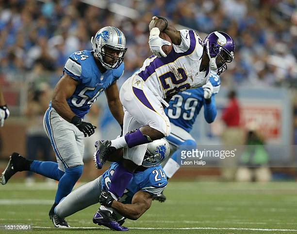 Adrian Peterson of the Minnesota Vikings runs for a fshort gain as DeAndre Levy and Erik Coleman of the Detroit Lions attempt to make the stop during...