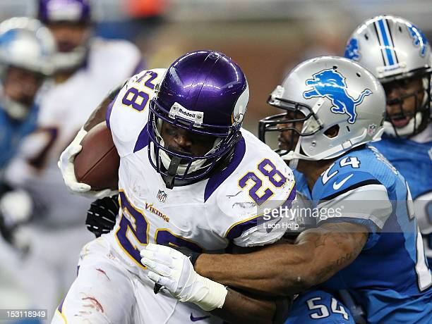 Adrian Peterson of the Minnesota Vikings runs for a short gain as Erik Coleman of the Detroit Lions makes the stop during the game at Ford Field on...