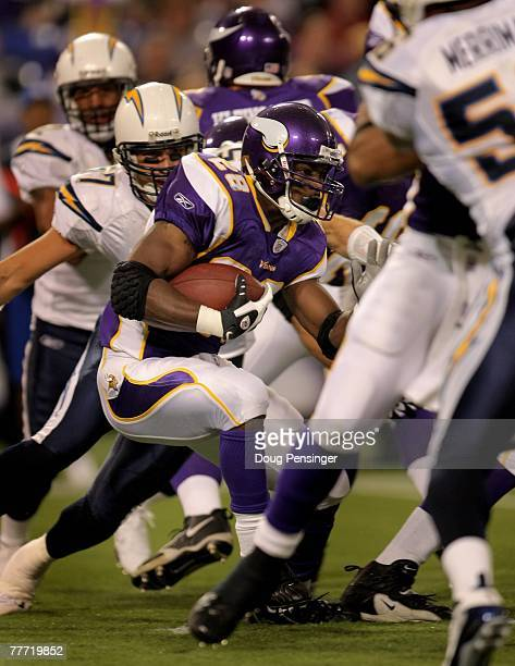 Adrian Peterson of the Minnesota Vikings runs the ball as he set two NFL records against the San Diego Chargers at the Hubert H Humphrey Metrodome on...