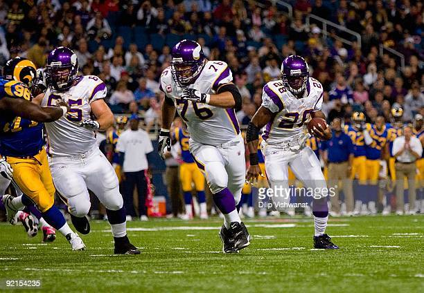Adrian Peterson of the Minnesota Vikings runs to his left toward the end zone in front of teammates Steve Hutchinson and John Sullivan during their...