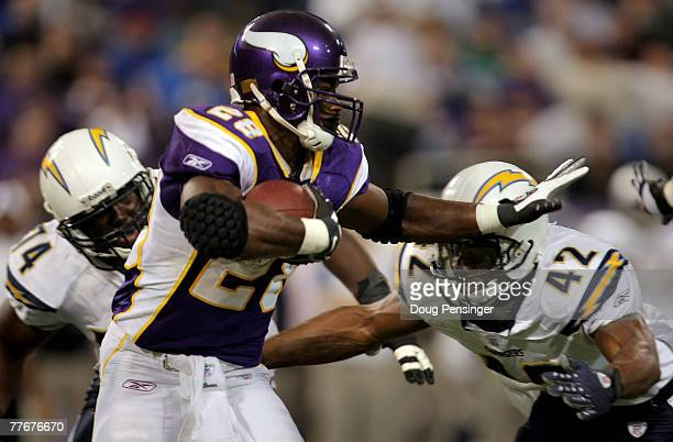 Adrian Peterson of the Minnesota Vikings rushes as Clinton Hart of the San Diego Chargers defends at the Hubert H Humphrey Metrodome on November 4...