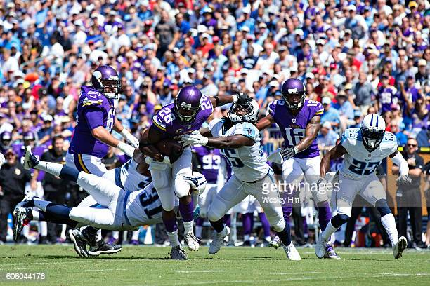Adrian Peterson of the Minnesota Vikings stiff arms Sean Spence of the Tennessee Titans at Nissan Stadium on September 11 2016 in Nashville Tennessee...
