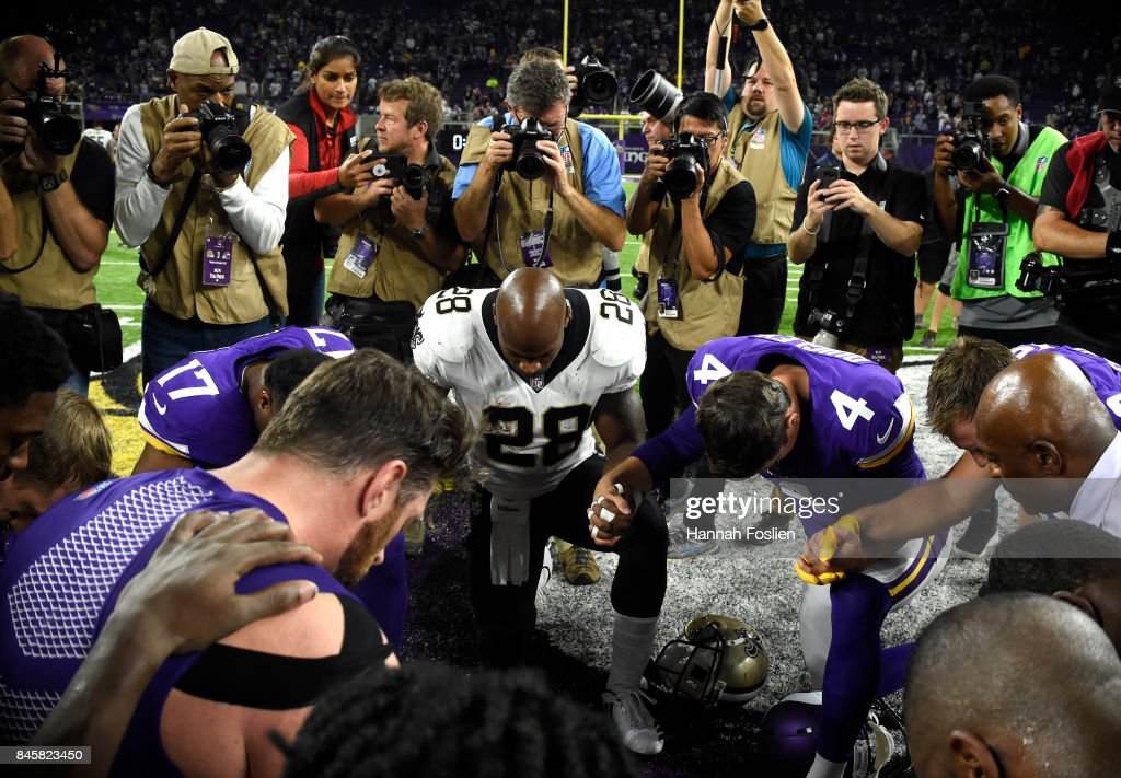 Adrian Peterson #28 of the New Orleans Saints and members of the Minnesota Vikings meet mid field after the game on September 11, 2017 at U.S. Bank Stadium in Minneapolis, Minnesota. The Vikings defeated the Saints 29-19 in Peterson's return to Minnesota.