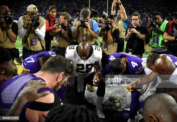 Adrian Peterson of the New Orleans Saints and members of the Minnesota Vikings meet mid field after the game on September 11 2017 at US Bank Stadium...