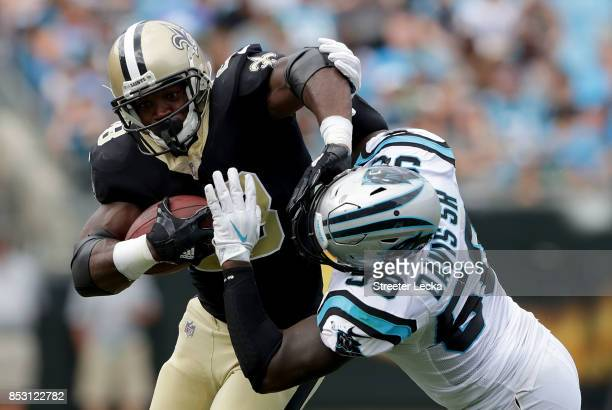 Adrian Peterson of the New Orleans Saints runs with the ball against Thomas Davis of the Carolina Panthers during their game at Bank of America...