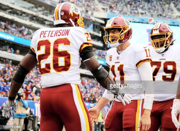 Adrian Peterson of the Washington Redskins celebrates his touchdown with quarterback Alex Smith in the fourth quarter against the New York Giants on...