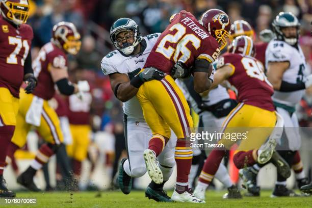 Adrian Peterson of the Washington Redskins is tackled by Brandon Graham of the Philadelphia Eagles during the first half at FedExField on December 30...
