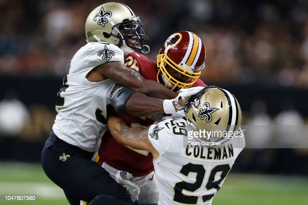 Adrian Peterson of the Washington Redskins is tackled by Kurt Coleman of the New Orleans Saints and Justin Hardee during the first half at the...