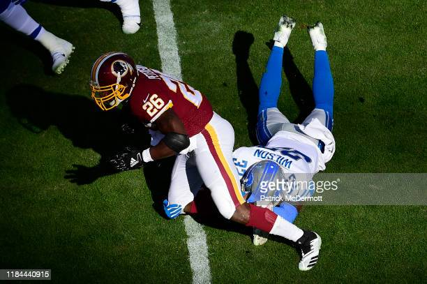Adrian Peterson of the Washington Redskins is tackled by Tavon Wilson of the Detroit Lions in the first quarter at FedExField on November 24 2019 in...