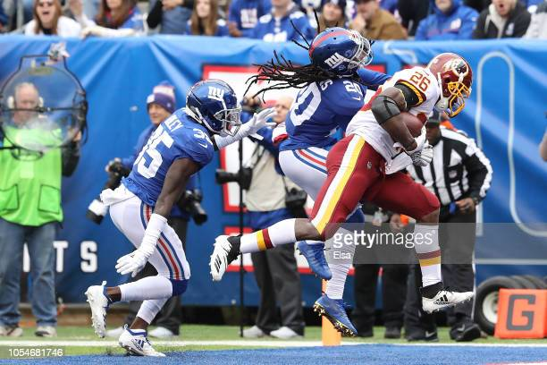 Adrian Peterson of the Washington Redskins scores a touchdown defended by Janoris Jenkins of the New York Giants during the first quarter at MetLife...