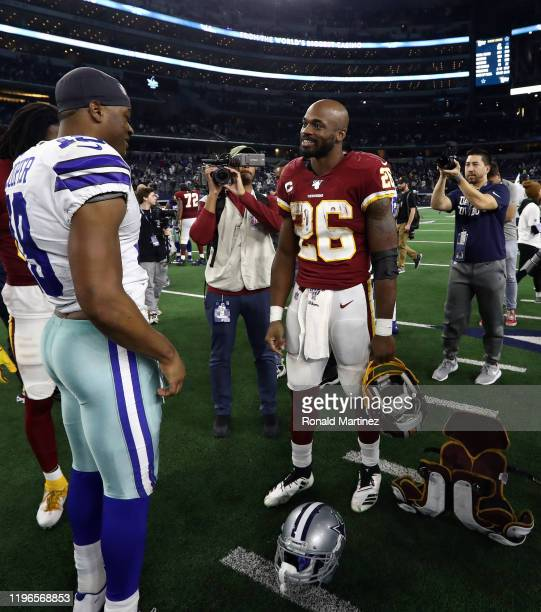 Adrian Peterson of the Washington Redskins with Amari Cooper of the Dallas Cowboys after the Cowboys defeated the Redskins 4716 at ATT Stadium on...