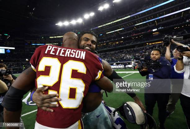 Adrian Peterson of the Washington Redskins with Ezekiel Elliott of the Dallas Cowboys after the Cowboys defeated the Redskins 4716 at ATT Stadium on...
