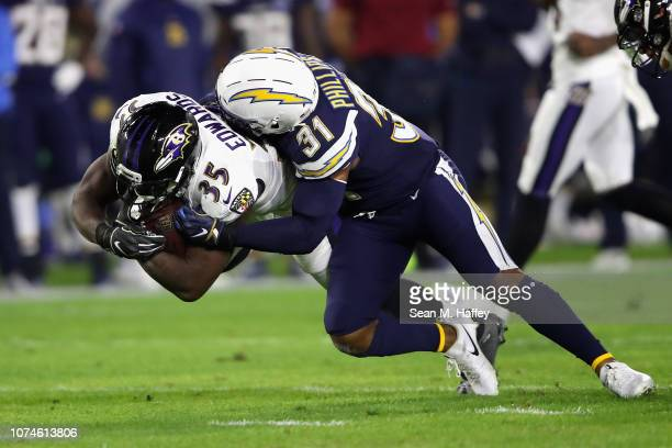 Adrian Phillips of the Los Angeles Chargers tackles Gus Edwards of the Baltimore Ravens on a running play during the first half of a game at StubHub...