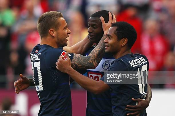 Adrian Ramos of Berlin celebrates his team's third goal with team mates Patrick Ebert and Raffael during the Bundesliga match between FSV Mainz 05...