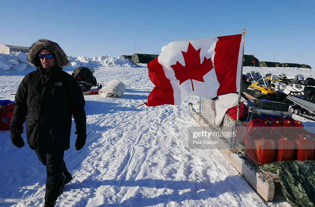 Adrian Schimnowski, project manager for the Arctic Research Foundation, passes some of the snowmobiles flown in for troops deployed in Operation NUNALIVUT, staged each winter to show Canadian sovereignty in the Arctic.