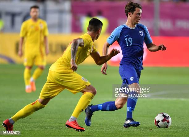 Adrian Stoian of Romania vies with Thomas Lam of Finland during the international friendly football match Romania v Finland in Ploiesti city June 5...
