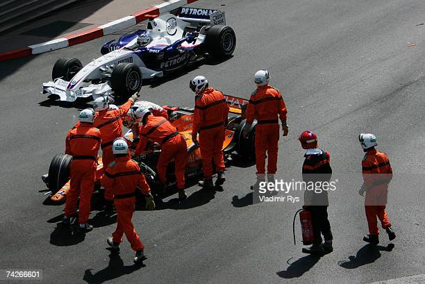 Adrian Sutil of Germany and Spyker F1 crashes as Nick Heidfeld of Germany and BMW Sauber passes by during the practice session for the Monaco Formula...