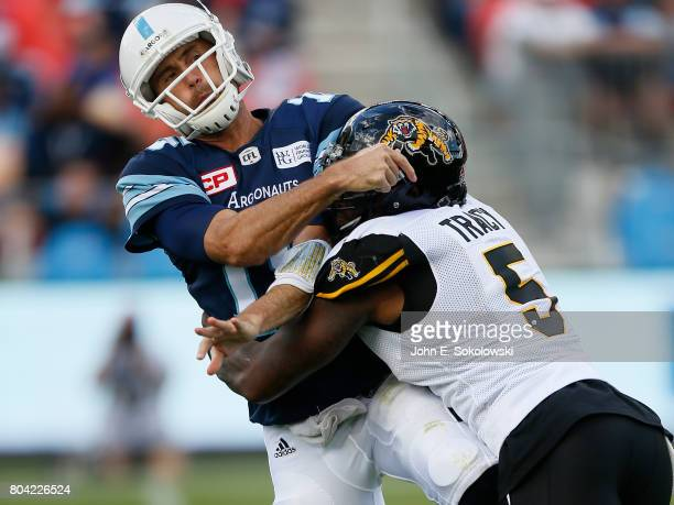 Adrian Tracy of the Hamilton TigerCats puts a hit on Ricky Ray of the Toronto Argonauts during a CFL game at BMO Field on June 25 2017 in Toronto...