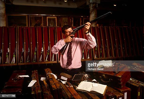 Adrian Weller the head of Sotheby's Sporting Gun department holds up a doublebarelled shotgun alongside a display of beautiful antique firearms and...