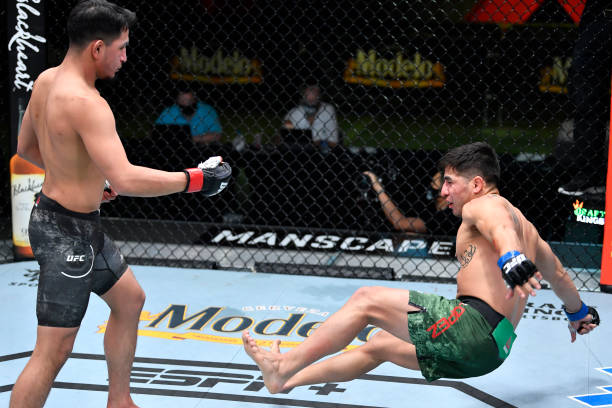 Adrian Yanez drops Gustavo Lopez with a punch in their bantamweight fight during the UFC Fight Night event at UFC APEX on March 20, 2021 in Las...