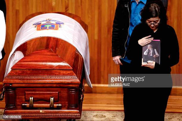Adriana del Paso, the daughter of Mexican writer Fernando del Paso, holds a book written by her father as she stands next to his coffin, during a...
