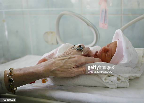 Adriana Iliescu caresses Eliza Maria her newborn girl at the intensive care department at the Giulesti Maternity Hospital in Bucharest 20 January...