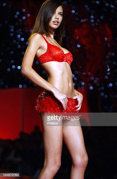 Adriana Lima wearing red embellished Victoria's Secret cherry blossom bra and red embellished micro fringe skirt