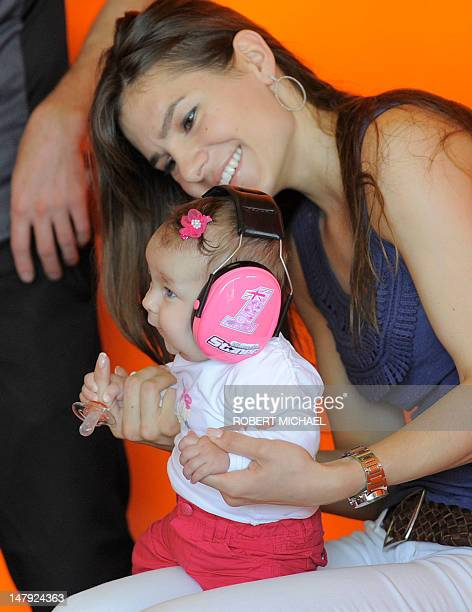 Adriana Stoner wife of Australia's Casey Stoner of the Repsol Honda team and her daughter look on prior to the first training session of the MotoGP...