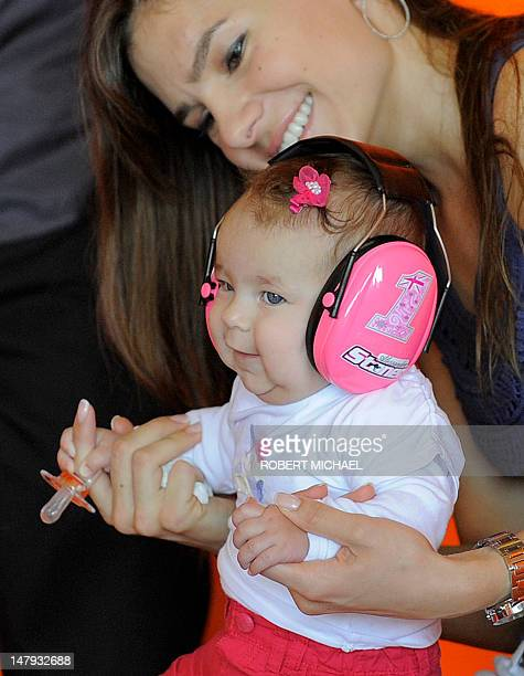 Adriana Stoner wife of Australia's Casey Stoner of the Repsol Honda team waits with their daughter prior to the first training session of the MotoGP...